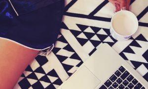 プライベートの女子がコーヒーを片手にパソコンを眺めている