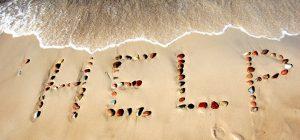 波際の砂浜にHELPと書かれている