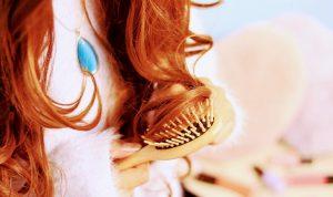 くしで髪をほどいている女性