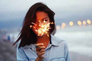 片手に花火を持ってこちらを見ているポジティブな女性